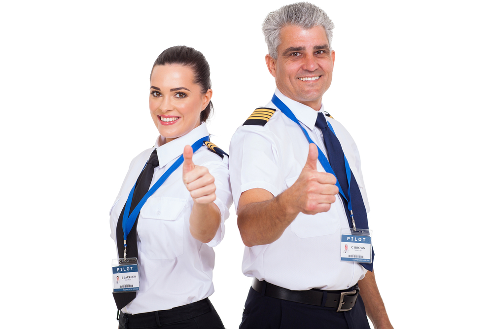 Two airline pilots standing side by side with a smile on their faces and a thumbs up.