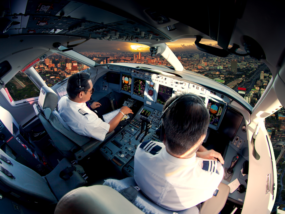 Two pilots in the cockpit flying over a city