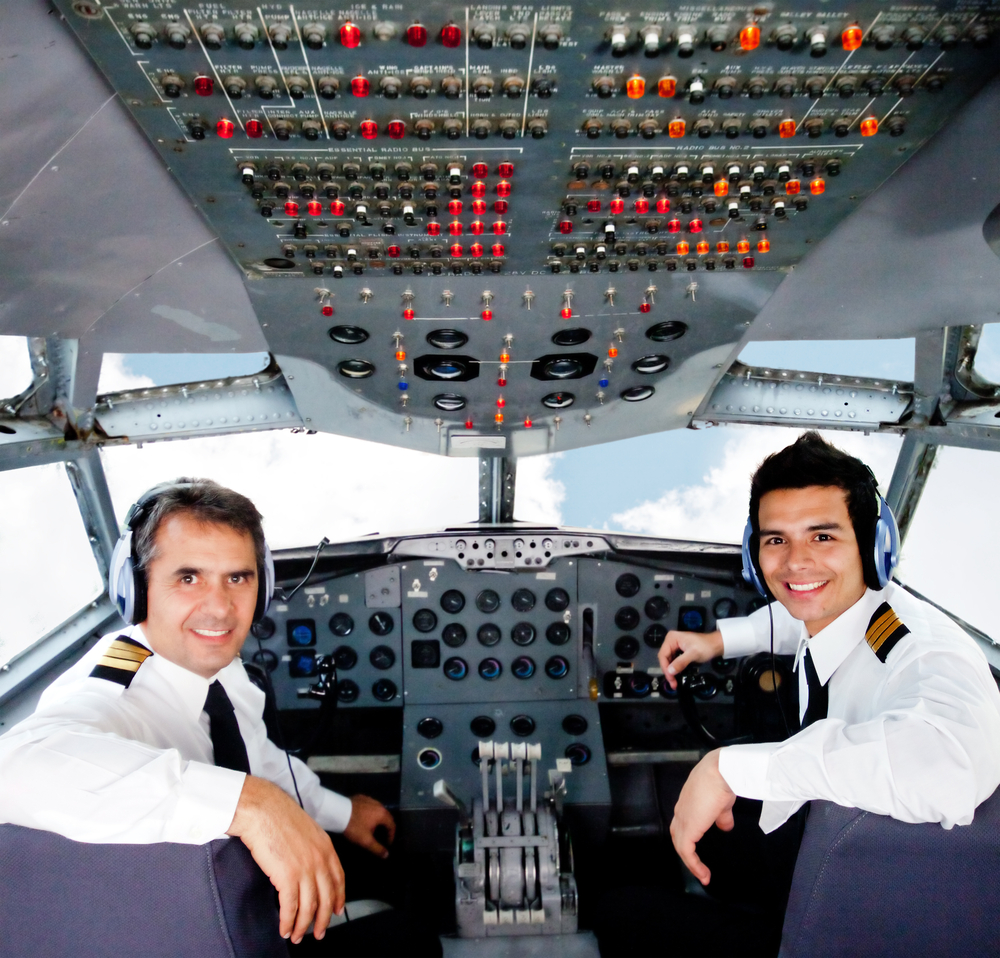 Two airplane pilots in a cockpit smiling